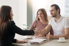 Молодая встреча пар семьи с маклером, рукопожатием символизируя a стоковое изображение