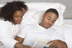 Молодая газета чтения пар совместно Стоковая Фотография
