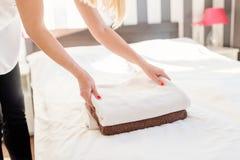 Молодая горничная гостиницы устанавливая свежие полотенца на кровати Стоковое Изображение RF