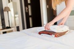 Молодая горничная гостиницы устанавливая свежие полотенца на кровати Стоковые Изображения