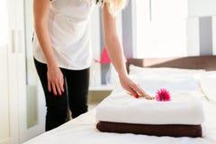 Молодая горничная гостиницы устанавливая цветок на свежих полотенцах Стоковое Изображение