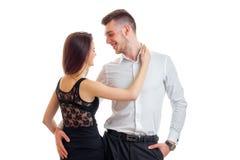 Молодая горячая девушка в черном платье обнимая шею красивого парня в рубашке Стоковые Фото