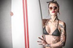 Молодая грубая женщина с татуировками с surfboard Стоковые Изображения RF
