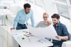 Молодая группа в составе архитекторы обсуждая бизнес-планы Стоковая Фотография