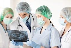 Молодая группа в составе доктора смотря рентгеновский снимок Стоковое Изображение RF