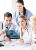 Молодая группа в составе доктора смотря рентгеновский снимок Стоковые Изображения RF