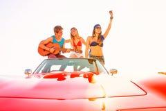 Молодая группа имея потеху на пляже играя гитару Стоковая Фотография