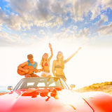 Молодая группа имея потеху на пляже играя гитару Стоковая Фотография RF