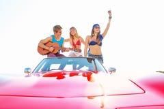 Молодая группа имея потеху на пляже играя гитару Стоковое Фото