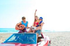 Молодая группа имея потеху на пляже играя гитару Стоковое фото RF