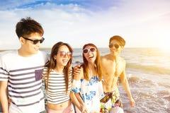 Молодая группа идя на пляж на летних каникулах Стоковое фото RF
