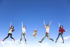 молодая группа скача вместе с собакой Стоковые Изображения
