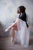 Молодая девушка балерины или танцора кладя на ее ботинки балета стоковое изображение rf
