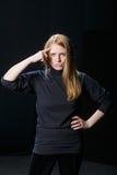 Молодая девушка белокурых волос подняла ее палец к ее голове против Стоковое Изображение RF
