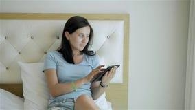Молодая девушка брюнет используя ПК таблетки лежа на кровати на утре видеоматериал