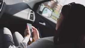 Молодая девушка брюнет сидя внутри управлять автомобилем на сиденье пассажира Выстучайте в телефоне swallowtail лета травы дня ба сток-видео