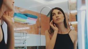 Молодая девушка брюнет смотря в зеркале в ванной комнате Проверять брови бобра акции видеоматериалы
