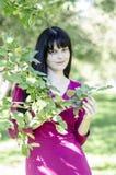 Молодая девушка брюнет с веснушками в красном платье в саде лета Стоковое Изображение RF
