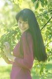 Молодая девушка брюнет с веснушками в красном платье в саде лета Стоковые Фотографии RF