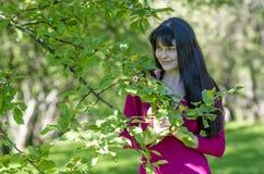 Молодая девушка брюнет с веснушками в красном платье в саде лета Стоковые Изображения RF