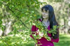 Молодая девушка брюнет с веснушками в красном платье в саде лета Стоковые Изображения