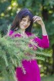 Молодая девушка брюнет с веснушками в красном платье в саде лета Стоковая Фотография