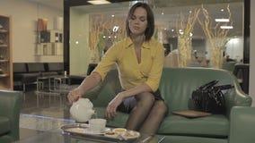 Молодая девушка брюнет льет чай в крышку в гостинице акции видеоматериалы