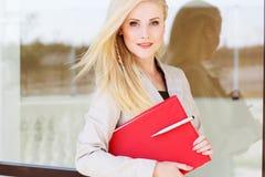 Молодая девушка менеджера с красной папкой и книгами стоковая фотография rf