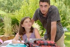 Молодая девушка подростка делая ее домашнюю работу с ее братом Стоковая Фотография RF