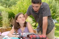 Молодая девушка подростка делая ее домашнюю работу с ее братом Стоковые Фотографии RF