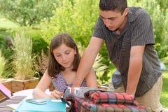 Молодая девушка подростка делая ее домашнюю работу с ее братом Стоковое Изображение