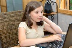 Молодая девушка подростка делая ее домашнюю работу с компьтер-книжкой Стоковые Фото
