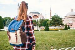 Молодая девушка путешественника с рюкзаком в квадрате Sultanahmet рядом с известной мечетью Aya Софии в Стамбуле в Турции Стоковое фото RF