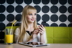 Молодая девушка студента выпивая апельсиновый сок стоковая фотография