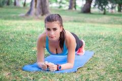 Молодая девушка фитнеса делая планку локтя во время разминки тренировки стоковые изображения rf