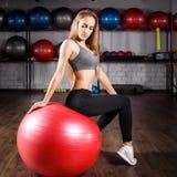 Молодая девушка фитнеса сидя на красном шарике Стоковая Фотография
