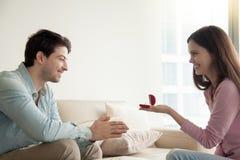 Молодая женщина давая обручальное кольцо, предлагая парня для того чтобы пожениться Стоковое Изображение