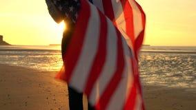 Молодая женщина Афро-американского подростка девушки женская на пляже обернутом в государственный флаг сша американском США сигна сток-видео