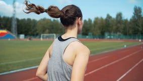 Молодая женщина бежать во время солнечного дня на следе стадиона акции видеоматериалы