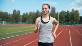 Молодая женщина бежать во время солнечного дня на следе стадиона видеоматериал