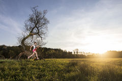 Молодая женщина бежать в заход солнца Стоковое Изображение RF