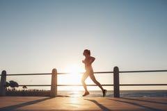 Молодая женщина бежать вдоль моря во время захода солнца Стоковая Фотография RF