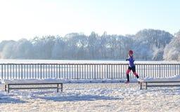 Молодая женщина бежать в снеге зимы стоковое фото