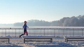 Молодая женщина бежать в снеге зимы стоковые изображения