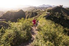 Молодая женщина бежать на китайской Великой Китайской Стене Стоковое Изображение