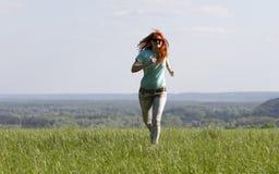 Молодая женщина бежать на луге весны Стоковое Изображение