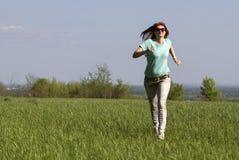 Молодая женщина бежать на луге весны Стоковая Фотография