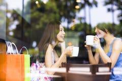 Молодая женщина 2 беседуя в кофейне Стоковая Фотография