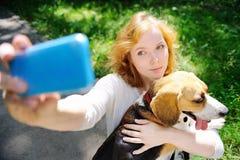 Молодая женщина битника делая фото selfie с собакой бигля Стоковое Изображение