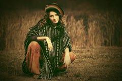 Молодая женщина битника моды сидя на траве внешней Стоковая Фотография